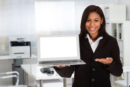woman work: Portrait of young businesswoman gesturing while holding blank laptop in office