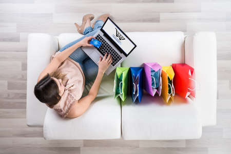 buy online: High Angle View Of Young Woman Shopping Online With Credit Card On Laptop