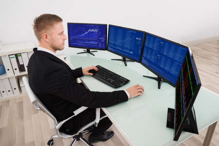 Młody Biznesmen Patrząc Na Wykres Na Wiele Ekranu Komputera