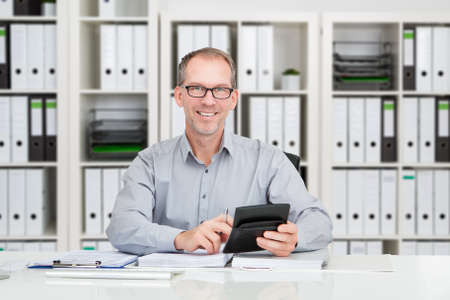 account executive: Portrait of confident mature accountant using calculator to calculate finance at desk in office