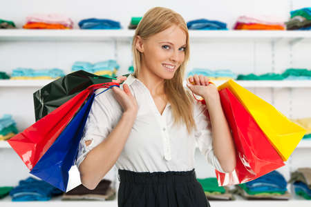 Portrait of happy young woman carrying shopping bags in store photo