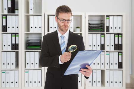 irregularity: Young businessman looking at document through magnifying glass in office