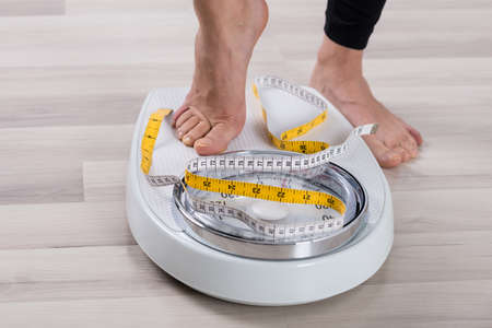 weight machine: Close-up Of Person Feet Standing On Weighing Scale Stock Photo