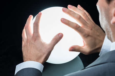 soothsayer: Cropped image of businessman predicting future on crystal ball against black background Stock Photo