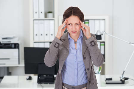 suffering: Young businesswoman suffering from headache in office Stock Photo