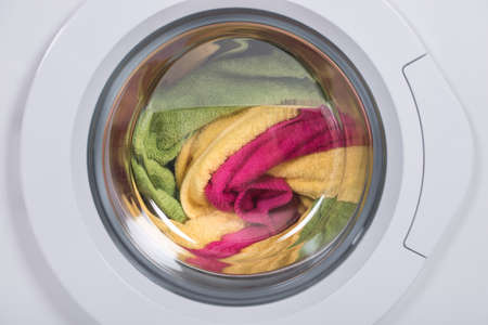 machine: Closeup of washing machine full of dirty clothes Stock Photo