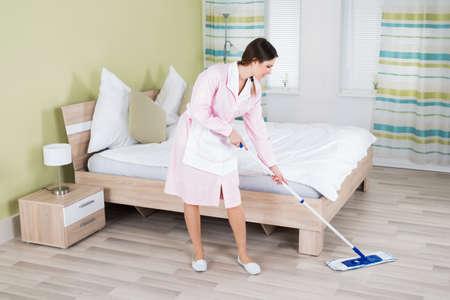 orden y limpieza: Mujer joven ama de casa limpieza del piso con la fregona en la habitación Foto de archivo