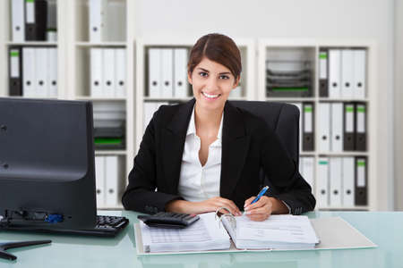 Portrait of confident female accountant writing on documents at desk in office