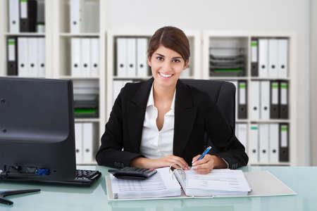 contabilidad financiera: Retrato de confianza de escritura contable de sexo femenino en los documentos en el escritorio en la oficina