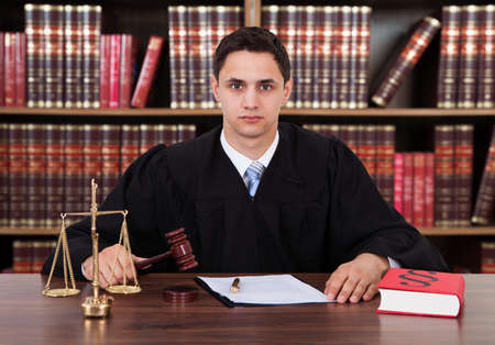 striking: Portrait of confident young male judge striking the gavel at table against bookshelf