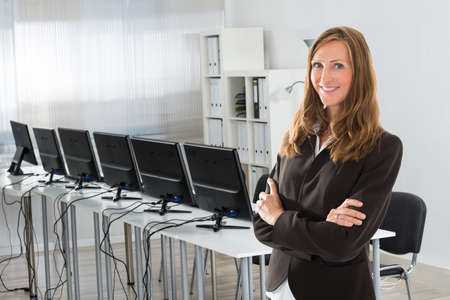 mid adult   female: Portrait of mid adult female manager standing arms crossed in office