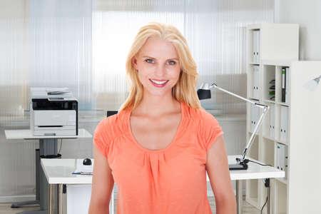 mujer bonita: Retrato de la empresaria hermosa joven sonriente en la oficina Foto de archivo