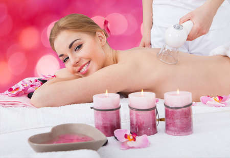 Portrait of happy young woman receiving cupping massage at beauty spa photo