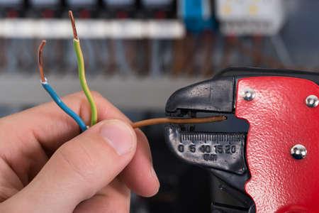 Close-up d'électricien mains dénudant les fils électriques