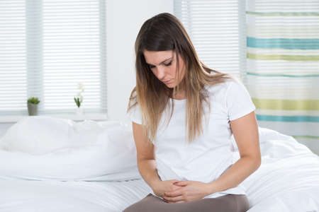 Unhappy Young Woman Suffering From Stomach Ache Sitting On Bed