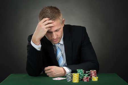 チップやカード テーブルの上で落ち込んでいる男性ポーカー