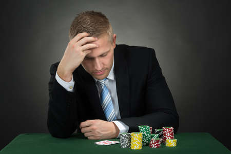 problem: Depressed Male Poker With Chips And Cards On Table