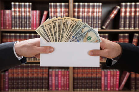 insincere: Cropped image of mans hands passing bribe to judge in envelope at courtroom