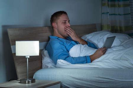sleepy man: Sleepy Man Yawning On Bed Looking At Laptop Stock Photo