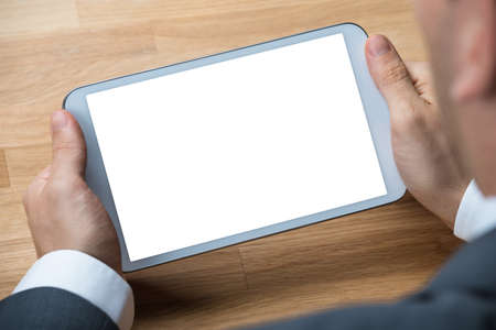blank tablet: Cropped hands of businessman holding digital tablet with blank screen at desk
