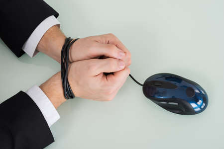 gefesselt: Close-up Person Handgelenk gebunden mit Computer-Maus-Kabel Lizenzfreie Bilder