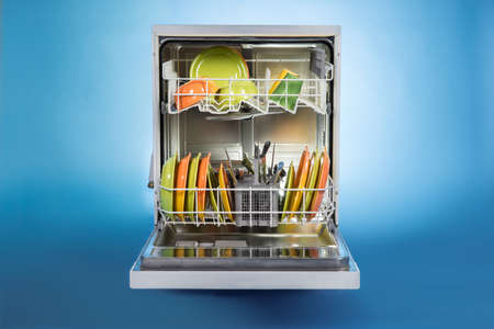 Dishwasher full of utensils isolated against blue background
