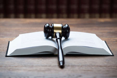 proceeding: Closeup of mallet on open legal book at table in courtroom Stock Photo