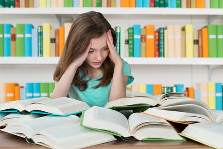 overburdened: Overburdened schoolgirl looking at books while studying in library