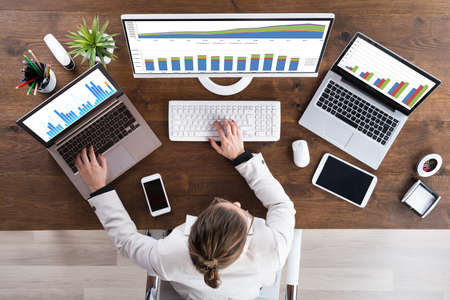 Vue en plongée de Jeune femme d'affaires Travailler avec des graphiques sur ordinateur Banque d'images