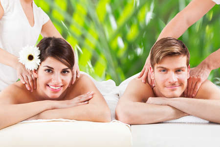 Portrait of happy young couple receiving shoulder massage at spa