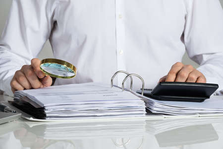 fraud: Midsection of businessman examining invoice with magnifying glass at office desk
