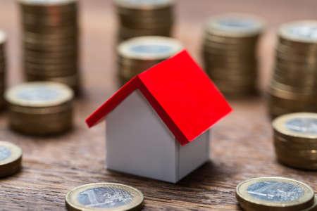 dinero: Modelo de la casa en medio de monedas apiladas en la mesa de madera