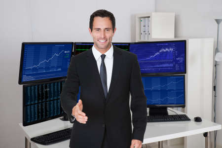 Portrait of confident stock broker offering handshake against multiple monitors in office photo