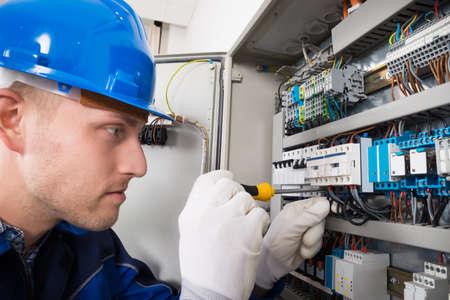 Mężczyzna robocza Elektryk Na Fusebox wkrętarką