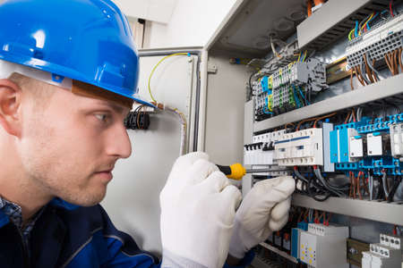 electrician tools: Male Electrician Working On Fusebox With Screwdriver Stock Photo