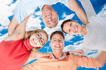 arms around: Directly below portrait of happy friends forming huddle against sky