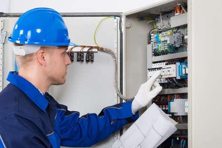Hombre electricista de exámenes Fusebox Con Blueprint En Mano Foto de archivo