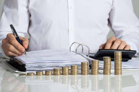 Midsection van zakenman het berekenen van de factuur met gestapelde munten gerangschikt bij bureau