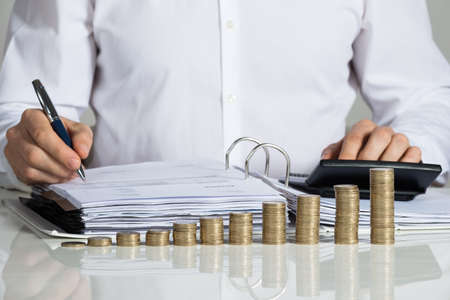 Midsection of businessman calculating invoice with stacked coins arranged at office desk