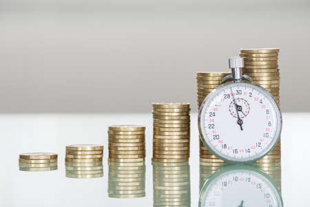 timekeeping: Close-up Of Stopwatch And Stacked Coins On Desk