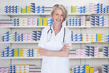 mature women: Portrait of mature female pharmacist standing arms crossed in pharmacy Stock Photo