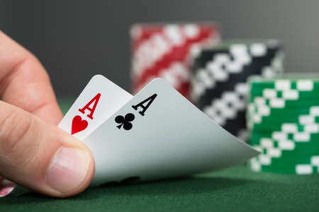 poker player: Close-up Of Poker Player Lifting Two Cards