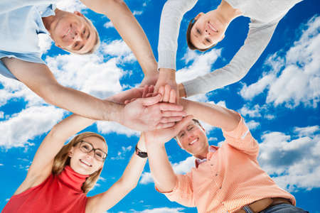 directly below: Directly below portrait of friends stacking hands while standing in huddle against sky