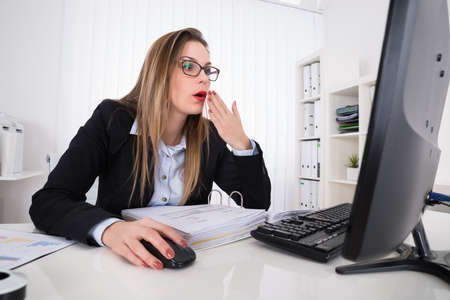 trouble: Young Shocked Businesswoman Looking At Computer On Desk Stock Photo