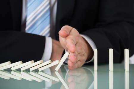 Close-up Van Businessperson stoppen Dominos Falling On Desk