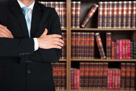 Midsection of lawyer with arms crossed standing against books in shelves