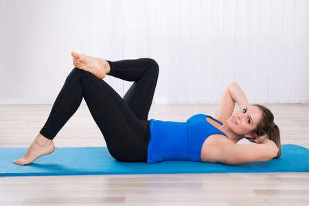 Mujer que se resuelve en la estera de ejercicios en clase de yoga Foto de archivo