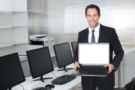 Portrait of mid adult businessman showing laptop with blank screen by desk in office photo