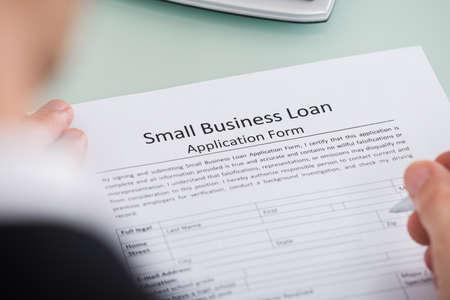 Close-up van de persoon die Overhandig Small Business lening Aanvraagformulier