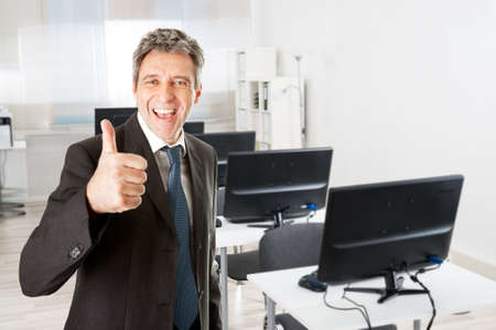 Portrait of mature businessman showing thumbs up sign by desk in office photo